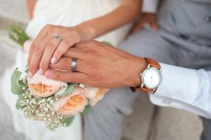 A couple holding hands dressed in wedding clothes