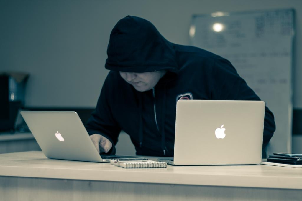 Man in black on two laptops who looks like he might be a hacker