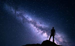A person ponders the galaxy appearing in the night sky.