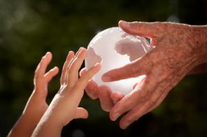 A chrystal glob passing from an old woman's hands to those of a child.