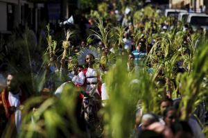 Jesus, riding a donkey, is nearly obscured by the palm-waving Palm Sunday crowd.
