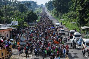 Migrants on foot fill a road that stretches off into the distance.