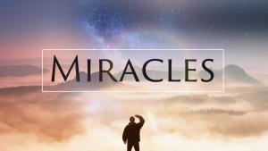 """A small human figure against a sun-lit cloudy sky with the legend """"Miracles"""""""