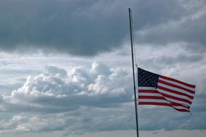 The Stars and Stripes at half-staff against a cloudy sky.