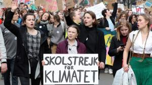 "Greta Thunberg, surrounded by young protesters, holds a sign ""Skolstrejk for Klimatet."""