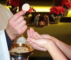A Communion minister places the consecrated host into waiting hands.