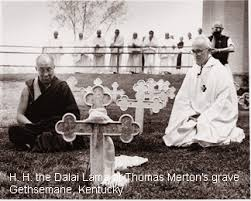 The Dalai Lama kneels before the cross marking Thomas Merton's grave.