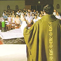 A priest faces the assembly during the concluding rite.