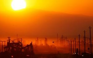 A field of oil rigs backlit by the orange glow of sunset and polluted sky.