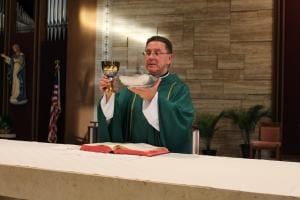 The priest holds the Eucharistic Bread and Cup as he says the words of the Doxology.