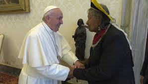 Pope Francis and Raoni Metuktire grasping each other's hands.