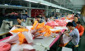 A long table, piles of material and workers participating in a supposedly free market economy.