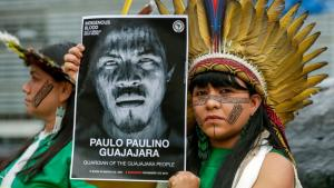 Woman with painted face wearing feathered headdress holds poster of Paulo Paulino Guajajara.