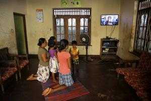 Family members at home kneel before a TV broadcasting Mass.