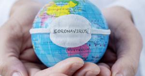 "Two hands hold a globe of the world on which is placed a bandage with the word ""coronavirus."""