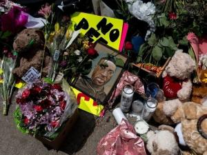 The site where George Floyd was killed is adorned with flowers, signs, and a picture of Floyd.