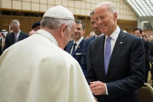 Pope Francis and Joe Biden shake hands. Several meeting participants look on in the background.