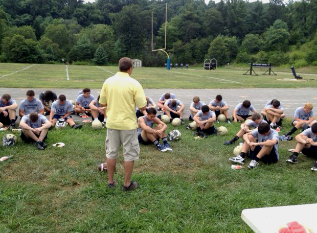 Football practice at public school Hidden Valley High School in Roanoke County: the team bows heads in prayer led by Thomas Brown with the Fellowship of Christian Athletes (Image via Facebook)